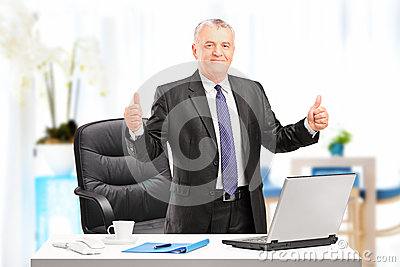 Businessman giving thumbs up in his office