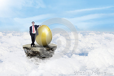 Businessman and gold egg on clouds