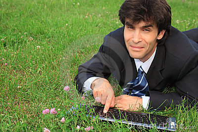 Businessman on grass with keyboard