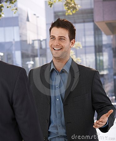 Businessman greeting colleague at office