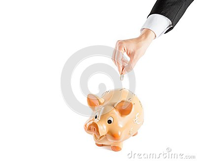 A businessman hand inserting a coin into a piggy bank isolated, concept for business and save money