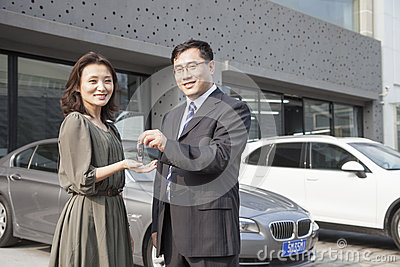 Businessman Handing Car Keys To Woman in Auto Repair Shop