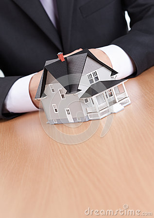 Businessman hands behind house model