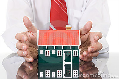 Businessman hands protecting a house