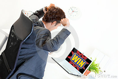 Businessman with hands raised up looking on laptop