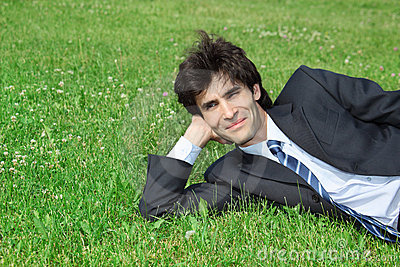 Businessman has rest, lying on grass