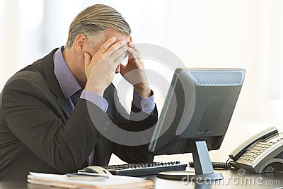 Businessman With Head In Hands Sitting At Desk
