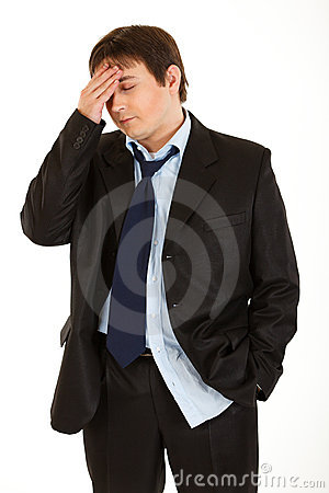 Businessman with headache holding hand at head