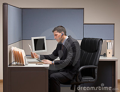 Businessman with headset working at desk in cubicl