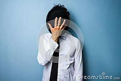 Businessman hiding his face behind a bowler hat