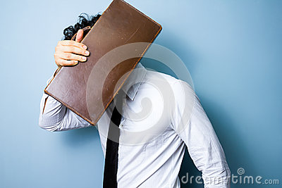 Businessman hiding his face behind an old briefcase