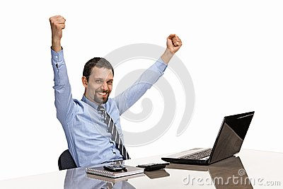 Businessman with his hands raised while working on laptop