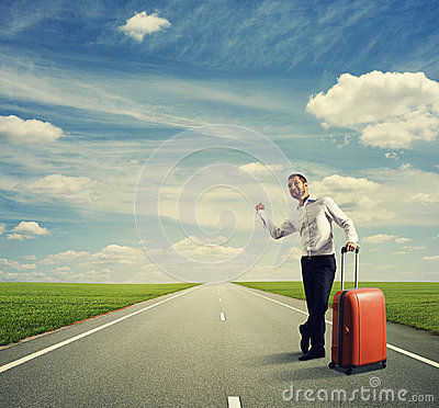 Businessman hitch hiking on a road