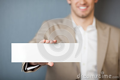 Businessman Holding Blank Sign Against Blue Wall