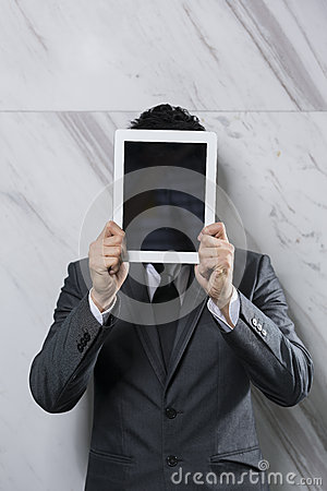 Businessman holding a digital tablet up over his face.