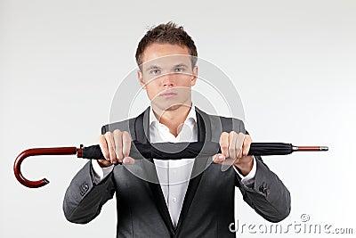 Businessman holding a folded umbrella