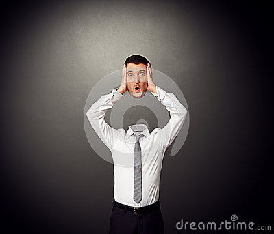 Businessman holding his amazed head in hands
