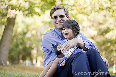 Businessman holding his son on grass