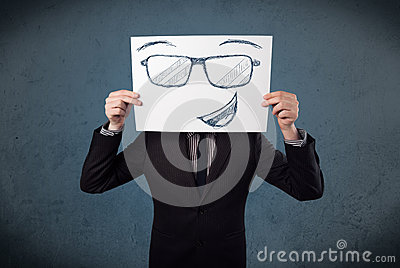 Businessman holding a paper with smiley face in front of his hea Stock Photo