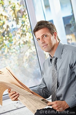 Businessman holding papers looking at camera