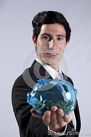Businessman holding a piggybank full of coins