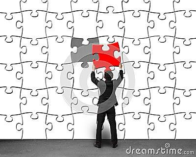 Businessman holding unique red puzzle assembling to white puzzle