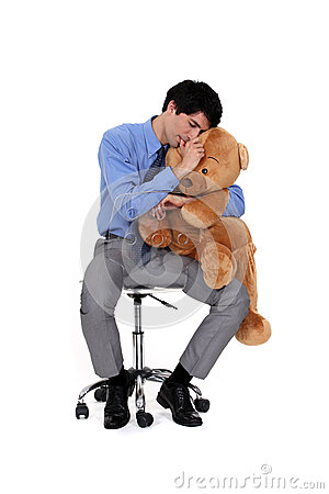 Businessman hugging a teddy bear.