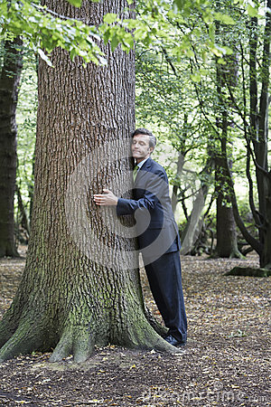 Free Businessman Hugging Tree Trunk In Forest Stock Photo - 33914360