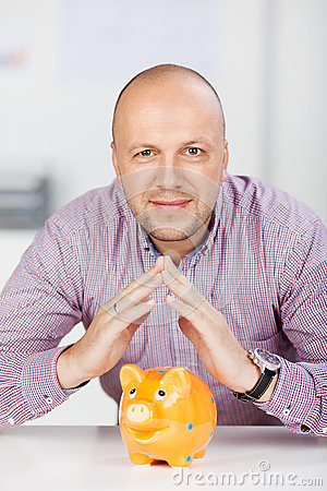 Businessman Joining Fingers Above Piggybank At Desk