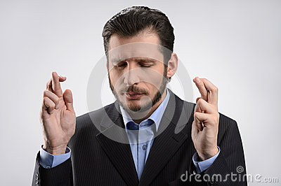 Businessman keeping his fingers crossed. Businessman standing wi