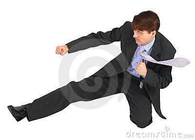 Businessman kicks forward on white background
