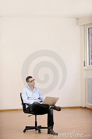 Businessman with laptop in new office