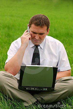 Businessman with laptop sitting in the grass