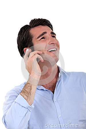 Businessman laughing over the phone.
