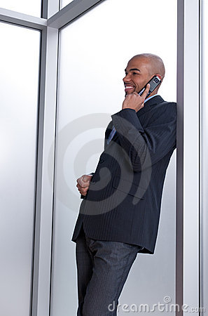 Businessman leaning against the window, talking