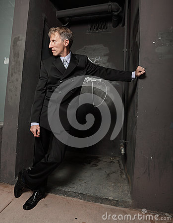 Businessman leaning on a wall at night