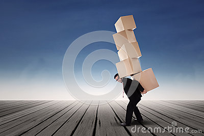 Businessman lifting boxes