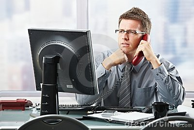 Businessman listening to landline call in office