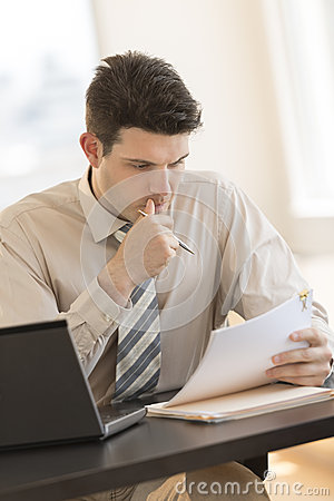 Businessman Looking At Documents While Sitting At Desk In Office