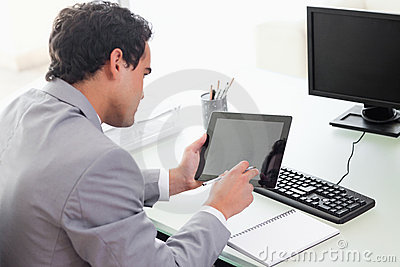 Businessman looking at his tablet in his office
