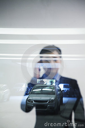 Businessman looking thorough window in parking garage, reflection of car