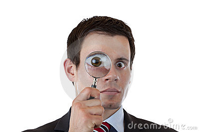 Businessman looks trhough magnifying lens