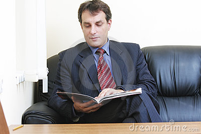 Businessman with magazine sitting on sofa