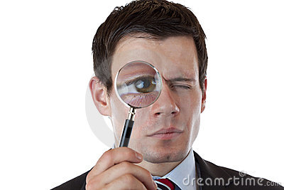 Businessman with magnifying glass at eye