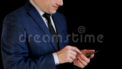 Businessman man in suit works on his smartphone, showing smile. Fingers touch the touch screen for typing. Management. And work through the Internet. The camera stock video footage