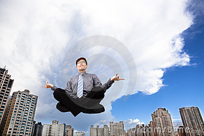 Businessman meditating in the air
