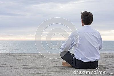 Businessman meditating at the sea