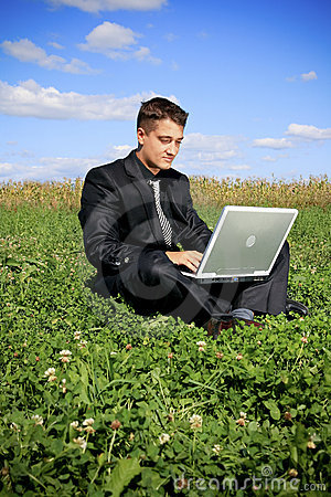 Businessman in the middle of the field on laptop