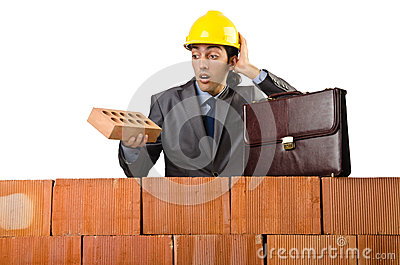 Businessman near brick wall