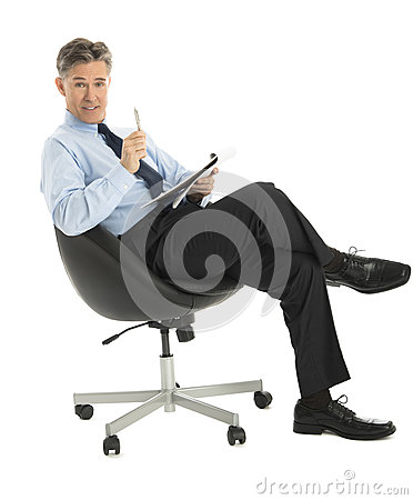 Businessman With Note Pad And Pen Sitting On Office Chair
